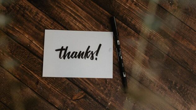 A white card with 'thanks!' written on it, placed on a dark wooden background, Next to it is a black pen.